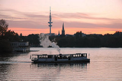 Sonnenuntergang an der Hamburge Alster - der historische Alsterdampfer St. Georg im Langen Zug - am Abendhimmel sind der Hamburger Fernsehturm zu erkennen.