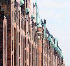 Fassade historischer  Speichergebäude in der Speicherstadt - die Winden am oberen Stockwerk sind mit einem kupfergedeckten Dach versehen