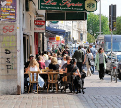 Aussengastronomie am Schulterblatt - Gäste eines Restaurants sitzen an Tischen auf dem Gehweg. Bilder aus dem Hamburger Stadtteil Sternschanze.