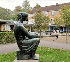 Bronzeskultur - sitzende Frau am Alten Teichweg in Hamburg Dulsberg.