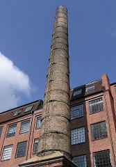 Hinterhof mit hohem Fabrikschornstein und Industriegebäude in Hamburg Sternschanze.