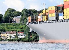 Bug des Containerschiffs MSC Faustina hochbeladen mit Containern - im Hintergrund Häuser am Strand von Oevelgönne und der Elbberg.