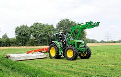 Bauer mit Trecker beim Wenden frischgemähten Gras auf einem Feld am Randes von Hamburg Lohbrügge.
