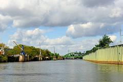 Veddelkanal in Hamburg Kleiner Grasbrook- rechts eine Spundwand als Hochwasserschutzanlage - lks. das Brandenburger Ufer mit in das Wasser hineingebaute Krananlagen.