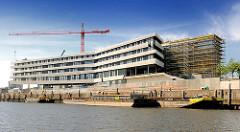 Baustelle der Hamburger HafencityUniversität  am Versmannkai im Hamburger Baakenhafen - Lastkähne liegen an der Kaimauer.