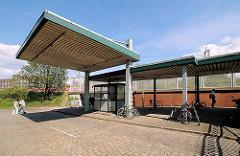 Verlassene Zollstation in Hamburg Veddel - FussgängerInnen gehen über den Platz Richtung S-Bahn.
