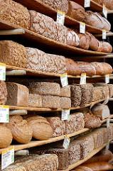 Biohof Gut Wulksfelde - Bauernmarkt. Aussteller präsentieren ihre Bioprodukte und Kunsthandwerk.  Frisch gebackenses Biobrot liegt in Holzregalen, die sich durch die Fülle biegen.