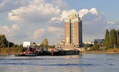 Ein Schubverband fährt von der Elbe in den Oberhafenkanal / Billehafen ein; rechts der Entenwerder Elbpark in Hamburg Rothenburgsort und im Hintergrund das Hochhaus vom Hotel Holiday Inn.