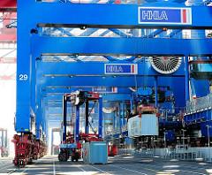 Ein Container wird gerade auf den Kai abgesenkt, eine andere Metallbox von einem Portalhubwagen aufgenommen - Bilder aus dem Hafen Hamburgs, Containerterminal Burchardkai.