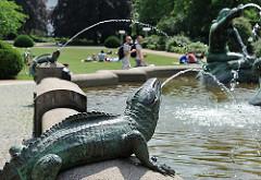 Wasserspeiende Figuren am Beckenrand des Stuhlmannbrunnense in Hamburg Altona - Liegewiese in der Sonne.