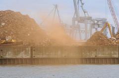 Arbeiten am Rosskai, Hafenbecken Rosshafen im Hamburger Hafen - Schrott, Altmetall wird auf Berge gestapelt - Staub weht über den Hafen.