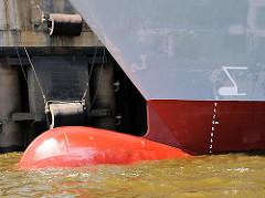 Wulstbug eines Containerschiffs im Hamburger Hafen; an der Kaimauer Fender aus Gummi, die die Bordwand des Schiffs beim Anlegen schützen sollen.
