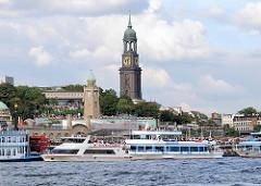 Blick auf die St. Pauli Landungsbrücken - Ausflugsschiffe liegen voll besetzt am Ponton - im Hintergrund der Uhrenturm der Landungsbrücken, dahinter die Jugendherberge und die St. Michaeliskirche.