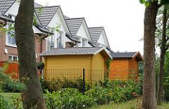 Moderne Wohnhäuser, Neubauten in Hamburg Langenbek - Gerätehäuser aus Holz im Garten.