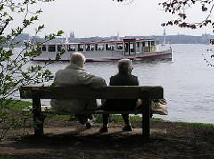 Parkbank  mit einem älteren Ehepaar am Alsterufer - ein Alsterschiff fährt vorbei.