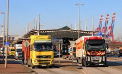 LKW haben die Zollgrenze und Zollstation des Hauptzollamt Waltershof durchfahren - im Hintergrund hochgefahrene Containerbrücken des Containerterminals Waltershof.