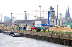 Kirchenpauerkai an der Norderelbe - Industriearchitektur; die Ladung eines Binnenschiffs wird gelöscht.