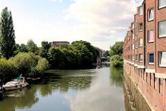 Wohnungen direkt am Wasser - Wohnhaus am Mittelkanal HH-Hamm; Sportboot am Liegeplatz; Bäume am Kanalufer.