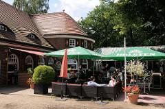 Biergarten im Hamburger Stadtpark - Gäste unter Sonnenschirmen im Landhaus Walter.