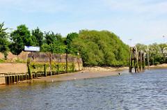 Kaimauer bei Niedrigwasser im Hamburger Hafen - der Bereich bei Hochwasser ist mit Algen bewachsen. Bei Ebbe zeigen sich die Baumstämme, die das Fundament der Kaianlage bilden.  Liegeplatz am Moldauhafen / Prager Ufer.