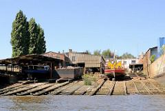 Alte Werftanlagen am Ufer des Reiherstiegs in Hamburg Steinwerder - Lastkähne und Barkassen liegen zur Reparatur auf der Slipanlage.