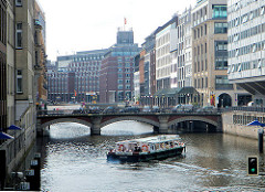 Ein Schiff einer Fleetfahrt biegt in das Bleichenfleet ein; dahinter die Adolphsbrücke in Hamburg Neustadt.
