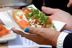 Biohof Gut Wulksfelde - Bauernmarkt. Aussteller präsentieren ihre Bioprodukte und Kunsthandwerk. Brot mit Lachs und Kräutern in den Händen einer Dame mit blau lackierten Fingernägeln.