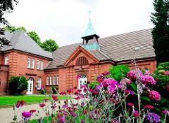 Gemeindehaus der Christ-König-Kirche in Hamburg Lokstedt; erbaut 1914; blühende Blumen in einem Beet.