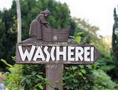 Holzschild geschnitztes Waschweib am Waschtrog - Wäscherei in HH-Nienstedten.