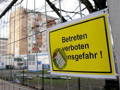 Schild am Bauzaun des abgesperrten Gebiets der Essohäuser an der Kastanienalle - Betreten verboten Lebensgefahr; im Hintergrund ein Umzugswagen und eines der sogen. Essohäuser.