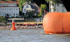 Wulstbug eines Frachtschiffs auf der Elbe vor Hamburg Othmarschen - im Hintergrund Strandbesucher bei der Strandperle am Elbufer.