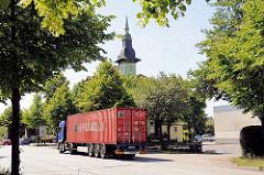 Containerlaster auf einer Strasse in Hamburg Wilhelmsburg - Giebelturm eines historischen Gasthauses am Wegesrand.