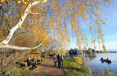 Spaziergänger in der Herbstsonne an der Bellevue im Hamburger Stadtteil Winterhude.