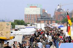 Menschenmenge auf dem Altonaer Fischmarkt - Touristenattraktion Hamburgs - im Hintergrund die Fischauktionshalle und Gebäude an der Großen Elbstraße.