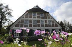 Historisches Fachwerkhaus - Reetdach, Blumen im Vorgarten.