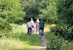 Familienausflug mit Rad - FahrradfahrerInnen auf einem Waldweg / Feldweg im Naturzschutzgebiet Höltingbaum.