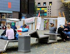 Beim St. Gertrudenfriedhof in der Hamburger Innenstadt / Altstadt - Sitzbänke und Zelte der Occupy Hamburg - Protestbewegung.