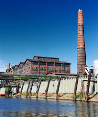 Architekturgeschichte im Hamburg Hafen - gewerbliche Gebäude am Müggenburger Kanal - hoher Ziegelschornstein.
