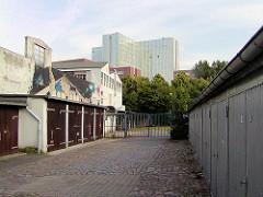 Garagen und Hinterhofbebauung in Hamburg Winterhude - Jarrestrasse in Hamburg Winterhude(2004); Abriss und Beginn der Neubebauung 2012 - im Hintergrund das Hochhaus der sogen. Alstercity.