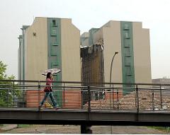Abriss des Lagergebäudes der Kaffeelagerei in der Hamburger Hafencity - im Vordergrund eine Passantin mit Regenschirm auf der Kibbelstegbrücke. (2006)