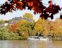 Blick über die Alster - zum Winterhude Ufer des Hamburger Sees - Herbstbäume am Alterufer - historischer Alsterdampfer St. Georg auf einer Rundfahrt.