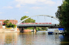 Blick in die Bille - eine S-Bahn fährt über die Eisenbahnbrücke von Hamburg Hammerbrook.