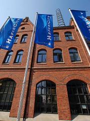Fahne mit dem Logo Hafencity vor dem Kesselhaus der Speicherstadt - Informationszentrum den neuen Hamburger Stadtteils Hafencity.