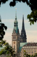 Blick über die Binnenalster zum Turm des Hamburger Rathauses, dahinter die Kriegsruine des Kirchturms der St. Nikolaikirche.