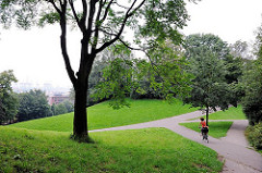 Hamburgs Grünanlagen und Parks - Donnerspark in Hamburg Ottensen - eine Fahrradfahrerin fährt den steilen Berg hinab.