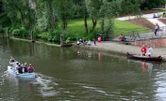 Blick von der Heinz-Gärtner-Brücke auf den Osterbekkanal - Kanu auf dem Wasser; Menschen am Ufer, Anleger in der Sonne.