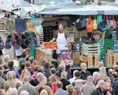 Verkaufsstand auf dem Hamburger Fischmarkt - ein Marktschreier preist seine Ware an.