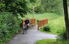 Brücke über die Engelbek - Holzbrücke über den Bach in Hamburg Langenbek; Radfahrer auf dem Weg.