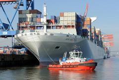 Schiffsbug der NYK HELIOS und roter Schlepper im Hamburger Hafen - Containerterminal Altenwerder. Das 2013 gebaute Containerschiff hat eine Länge von 365,50m und eine Breite von 48,40m; der Frachter kann 13208 TEU Container transportieren.