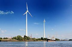 Windkraftanlage in Hamburg Wilhelmsburg - ein Frachter liegt auf der Süderelbe vor der Kattwykbrücke und wartet darauf, dass die Hubbrücke hochgefahren wird.